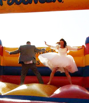 bride and groom jumping on a bouncy castle